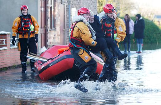 Members of the emergency services rescue a woman from a flooded street in Naburn, northern England Photo: Reuters