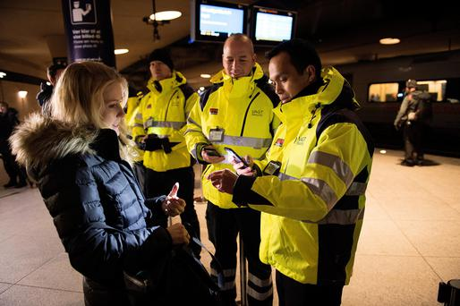 Security staff check ID at a Copenhagen train station
