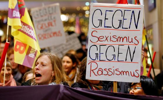 Protesters hold up a placard that reads 'Against Sexism - Against Racism' at Cologne railway station