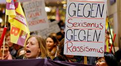 Women hold up a placard that reads 'Against Sexism - Against Racism' as they march through the main railway station of Cologne, Germany, yesterday. Photo: Reuters/Wolfgang Rattay