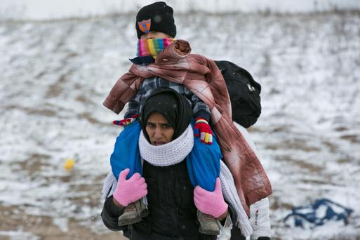A migrant mother carries her child as they walk through the snow from the Macedonian border into Serbia (AP)