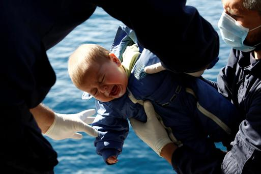 Greek coast guard officers move a baby from a dinghy carrying refugees to a coast guard vessel, during a rescue operation in the open sea between the Turkish coast and the Greek island of Lesbos.