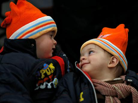 Two migrant twin brothers look at each other as they wait to continue their train journey to western Europe at a refugee transit camp in Slavonski Brod, Croatia