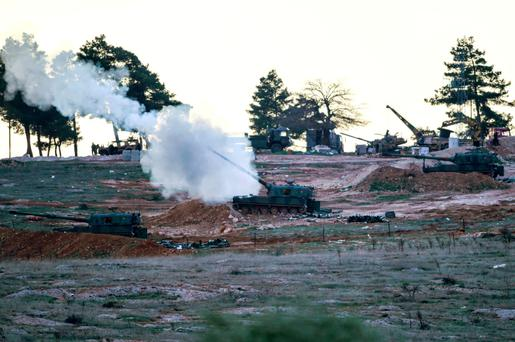 Tanks stationed at a Turkish army position near the Oncupinar crossing gate close to the town of Kilis, south central Turkey, fire towards the Syria border yesterday.