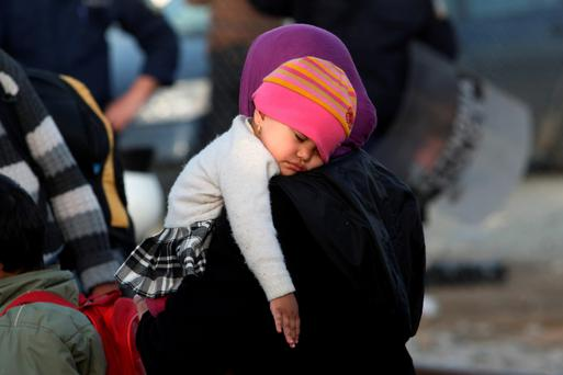 A toddler sleeps while refugees from Afghanistan wait to board a bus as Greek police move them from the Greek-Macedonian border near the village of Idomeni