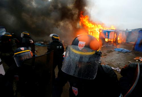 French riot police in the Calais migrant camp, known as the Jungle, as demolition of the camp resumes in Calais, France.