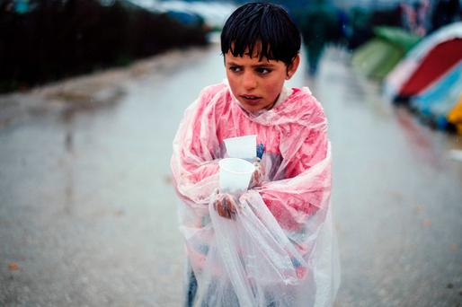 A migrant boy walks in the rain at a makeshift camp on the Greek-Macedonian border where thousands of refugees and migrants are stranded by the Balkan border blockade. Photo: AFP