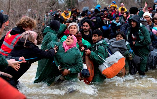 Hundreds of migrants cross a river after leaving the Idomeni refugee camp in Greece