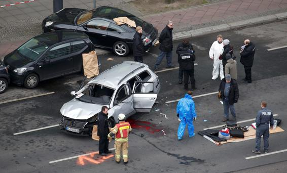 Police inspect the wreckage of the Volkswagen car after it exploded in Bismarckstrasse in Berlin