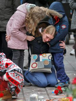 A woman consoles her children at a street memorial following Tuesday's bomb attacks in Brussels, Belgium