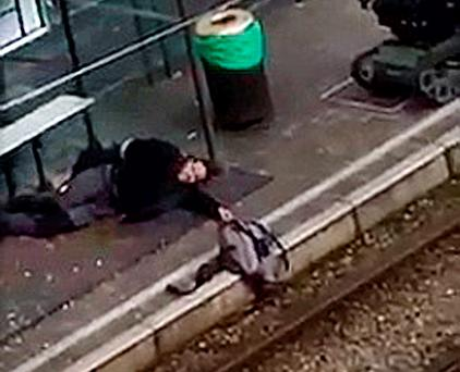 A suspect lies on the platform of a tramway station, in this image taken from amateur video, after he was shot and wounded by police in the Brussels borough of Schaerbeek following Tuesday's bombings in Brussels, Belgium,