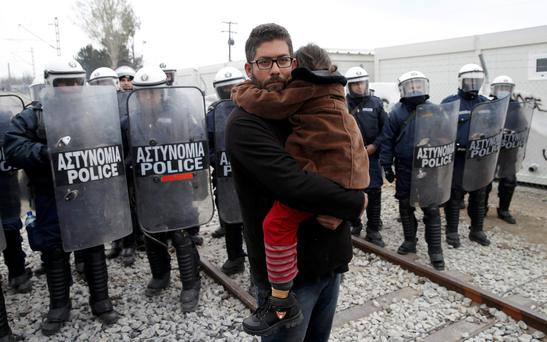 A migrant holds a child as he stands in front of Greek police during a protest at a makeshift camp at the Greek-Macedonian border near the village of Idomeni, Greece (Photo: Reuters/Marko Djurica)