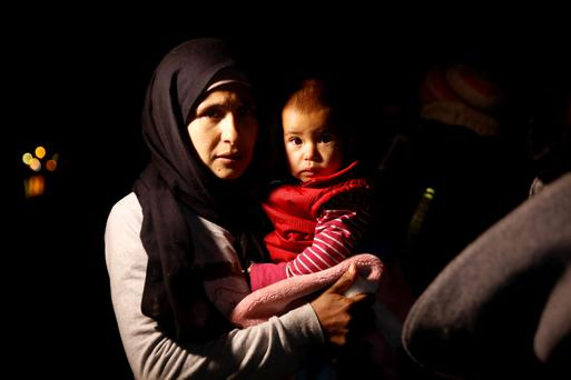 A woman holds her baby after disembarking at Lesbos. Photo: Louisa Gouliamaki/Getty