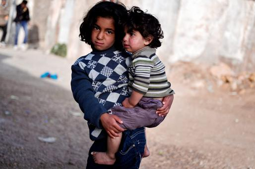 A girl carries her brother on the island of Chios. Photo: Reuters/Giorgos Moutafis,