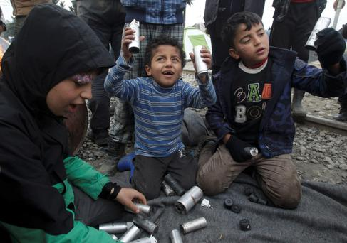 Migrant children play with rubber bullets and empty cases near Idomeni yesterday. Photo: Reuters