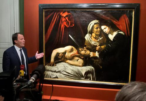 Auctioneer Marc Labarbe presents the recently discovered 'Judith Beheading Holofernes', thought to have been painted by Italian master Caravaggio, to the media in Paris yesterday