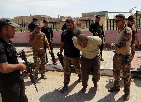 Iraqi security forces arrest a man suspected of being an Isil fighter during a military operation to regain control of Hit, 140 kilometers west of Baghdad, last week. Photo: AP/Khalid Mohammed