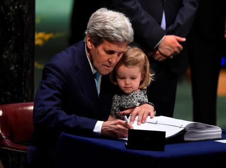 US Secretary of State John Kerry signs the book while holding his granddaughter, Isabelle Dobbs-Higginson, during the signature ceremony for the Paris Agreement at the United Nations General Assembly Hall yesterday in New York. Photo: AFP/Getty