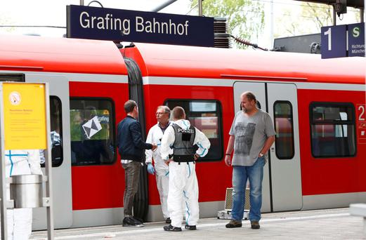 Police officers look for evidence at the train station after an attack in Grafing, southeast of Munich, Germany