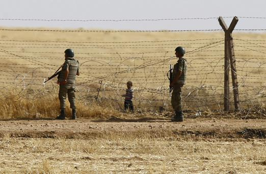 Turkish soldiers stand guard as a Syrian refugee boy waits behind the border fences to cross into Turkey on the Turkish-Syrian border, near the southeastern town of Akcakale in Sanliurfa province.
