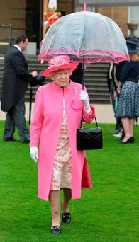 Queen Elizabeth shelters from the rain under the 'offending' umbrella at the first Royal Garden Party of the year in the grounds of Buckingham Palace. Photo: John Stillwell/Getty Images