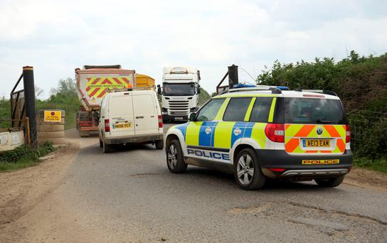A police vehicle enters Block Fen Quarry at Mepal, near Ely, in Cambridgeshire, where a severed head was discovered Monday. Photo: PA