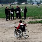 A boy on a wheelchair looks at riot police officers during an evacuation operation by Greek police forces of the makeshift camp at the Greek-Macedonian border, near the village of Idomen