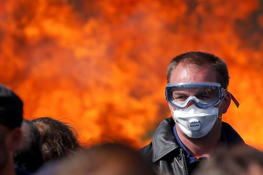A man wears a mask while a fire rages at an oil depot in Donges, western France, as striking workers are evacuated by riot police Photo: AFP