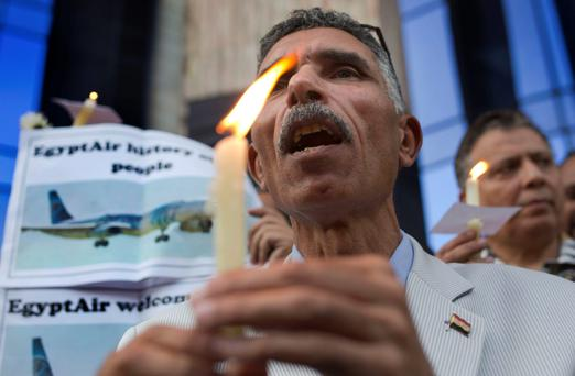A man holds a candle and a poster supporting EgyptAir during a vigil for the victims of flight MS804 in Cairo Photo: Amr Nabil