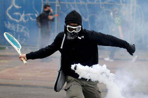 A protestor uses a tennis racket to return a tear gas canister during a demonstration to protest the government's proposed labour law reforms in Nantes