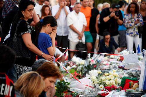 A child mourns as people gather next to flowers and candles placed in the road for victims of the deadly Bastille Day in Nice. Photo: Getty