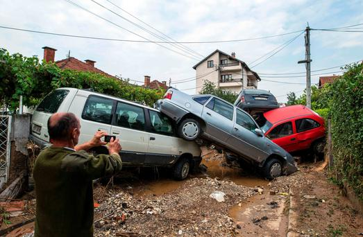 A local takes a photo of damaged vehicles following floods in the village of Stajkovci, near Skopje