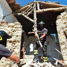 Firefighters recover a crucifix from a damaged church in the village of Rio, about 10km from the worst-hit town of Amatrice