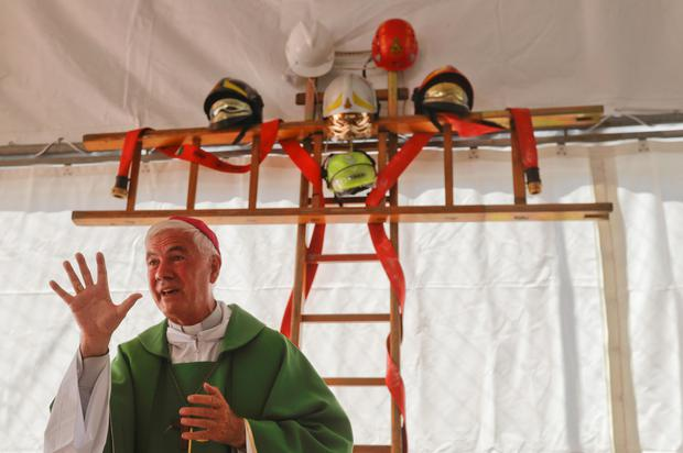 Bishop Giovanni D'Ercole celebrates Mass in a tent with a cross made from ladders and firefighter helmets at a camp for earthquake survivors in Arquata Del Tronto