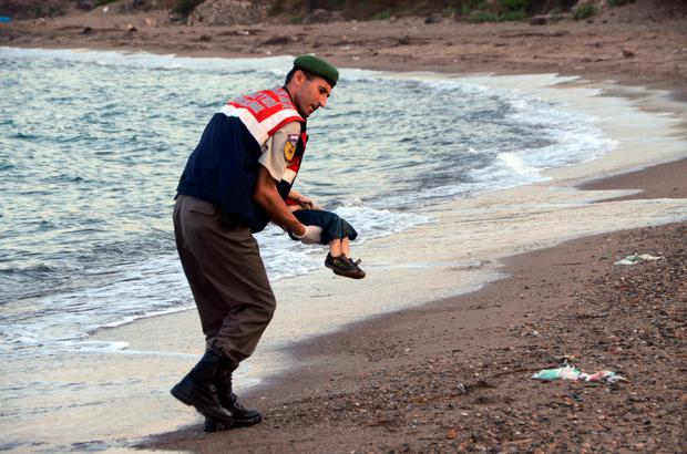 A Turkish policeman carries Aylan's lifeless body. Photo: AP