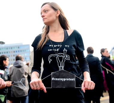 A woman takes part in a protest against a proposed near-total abortion ban in Poland in front of European institutions in Brussels