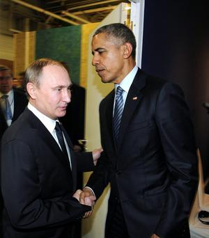 Frosty reception: Russian President Vladimir Putin (left) meets US President Barack Obama in 2015 at the World Climate Change Conference in France, where the temperature between the two was less than warm