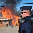 A French riot police officer stands by a shack set on fire during the demolition of the Calais