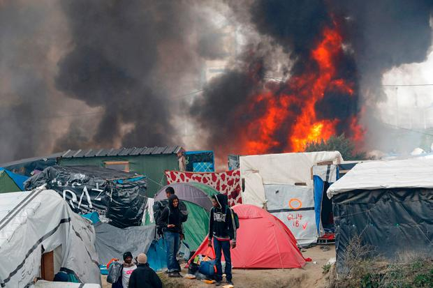 Migrants carry their belongings as they walk past burning makeshift shelters and tents in the