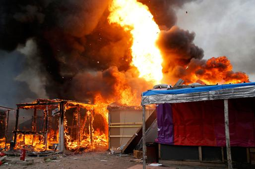 Flames from makeshift shelters shoot up into the sky after a gas bottle explodes in the Jungle as refugees saw their hopes of resettling in Britain come to an end. Photo: Reuters