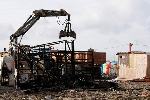 A bulldozer is used to remove debris as workmen tear down makeshift shelters during the dismantlement of the camp called the