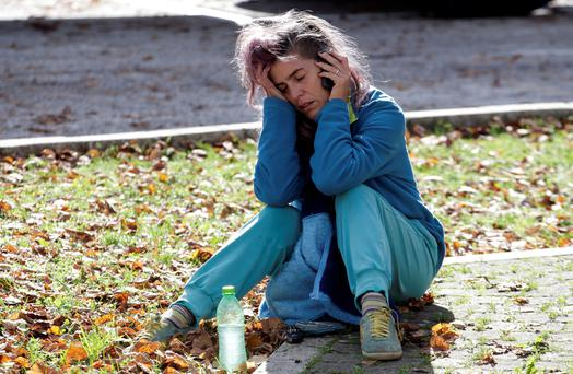 A woman makes a phone call as she sits on the ground after an earthquake in Ussita, central Italy