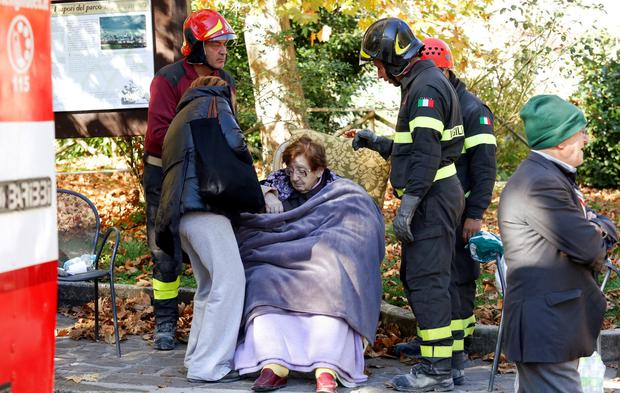 Firefighters take care of a woman in Norcia. Photo: Reuters