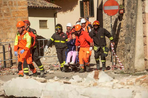 Firefighters and rescuers carry a woman on a wheelchair after the 6.5 magnitude earthquake in Norcia. Photo: Getty Images