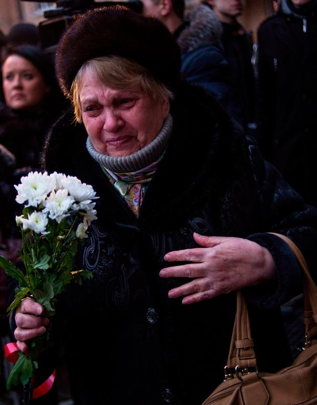 A woman in Moscow cries as she holds flowers at the home of the Alexandrov Ensemble (the Red Army Choir). Photo: Getty Images