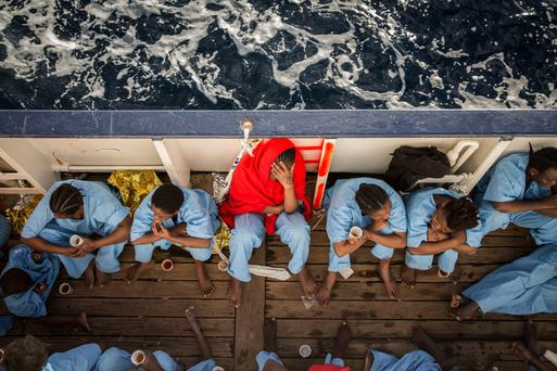 Migrants sit on the deck of the Golfo Azzurro vessel after being rescued from the Mediterranean sea, about 30km north of Libya at the weekend. Photo: AP