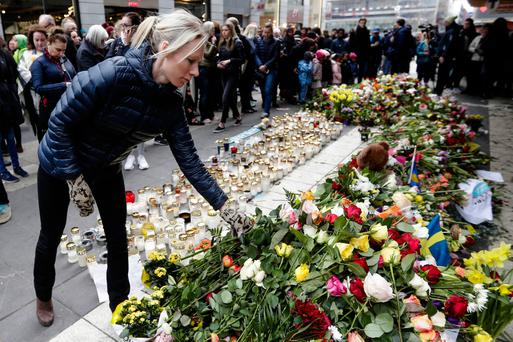 A woman lays flowers in front of the department store in Stockholm that was hit by the truck in the terror attack. Photo: AP
