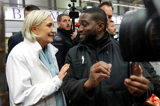 Marine Le Pen meets a worker at a food market in Paris yesterday. Photo: Reuters
