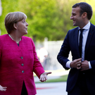 German Chancellor Angela Merkel and French President Emmanuel Macron talk as they arrive at a ceremony at the Chancellery in Berlin yesterday. Photo: Reuters