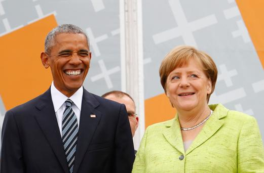 German Chancellor Angela Merkel and former U.S. President Barack Obama attend a discussion at the German Protestant Kirchentag in front of the Brandenburg Gate in Berlin, Germany, May 25, 2017. REUTERS/Fabrizio Bensch